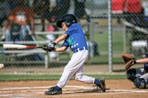 野球の試合でヒットを打つ少年