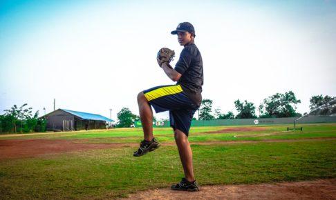 ピッチャーが足を上げボールを投げようとしている